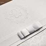Detalhe do brasão e do padrão exclusivos, e do laço Chanel duplo.