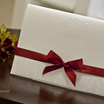 Convite de casamento com brasão exclusivo e acabamento em fita vermelha.