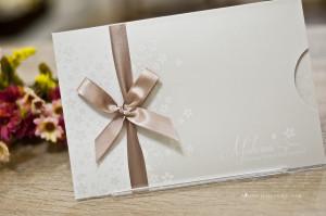 Convite de formatura com tema floral e acabamento em fita de cetim nude.