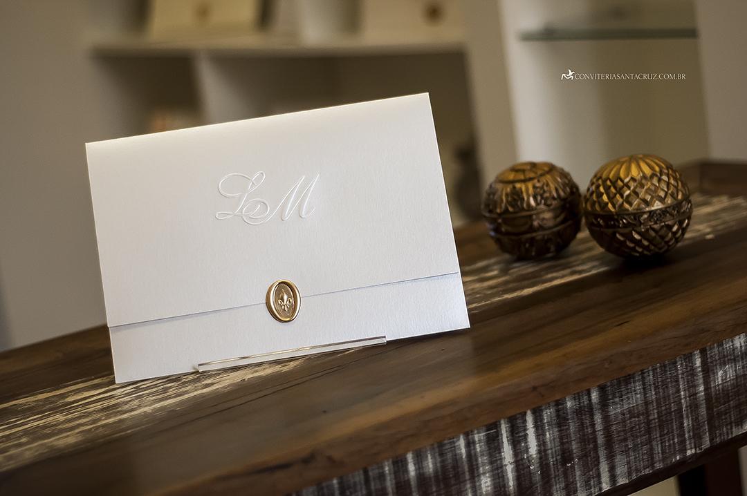 Convite de casamento em papel metalizado e lacre de cera dourado.
